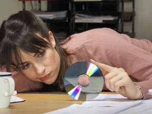 Young female office worker slumped at desk, toying with CD